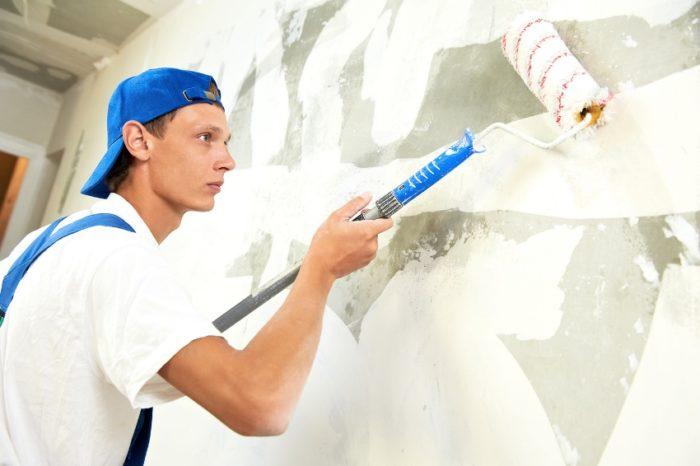 Грунтовка стен с использованием малярного валика на длинной ручке