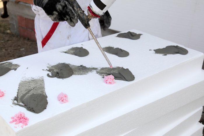 Листы пенополистирола крепятся к стене с помощью дюбелей или клея