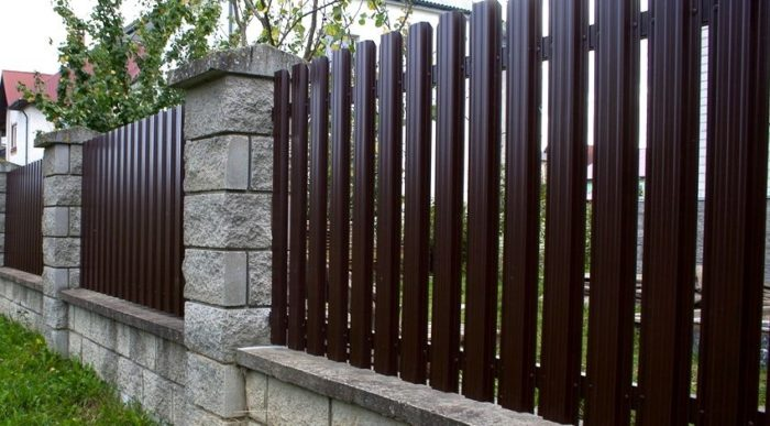Пример простого и стильного ограждения участка из евроштакетника с каменными опорами