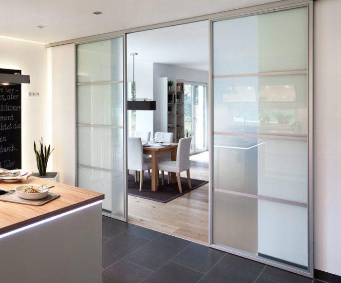 Двустворчатые двери-купе из полупрозрачного стекла между кухней и гостиной