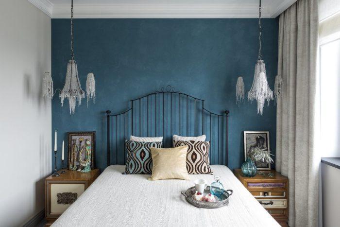 Стена у изголовья кровати, выполненная в акцентной манере с помощью цвета – удачный дизайнерский прием для выделения центрального предмета мебели маленькой спальни