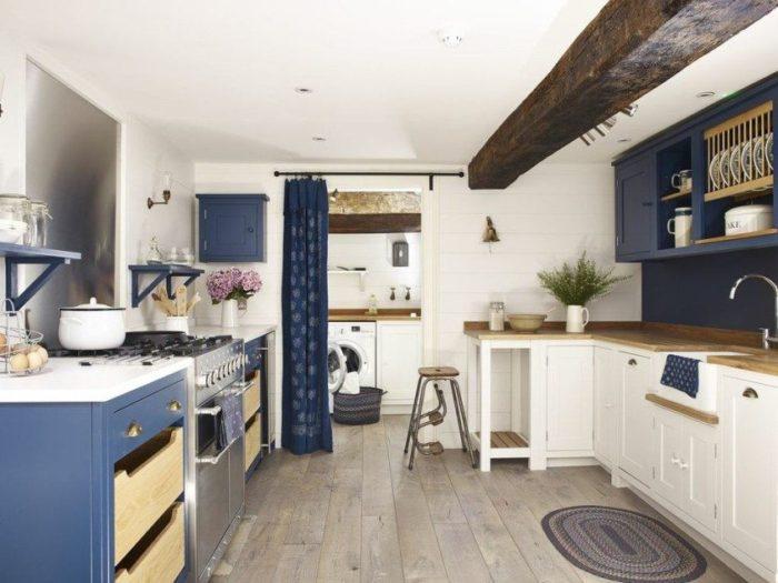 Дверной проем между кухней и кладовой оформлен с помощью настенного карниза и шторы