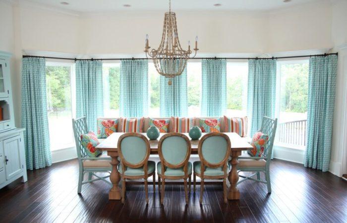 Для оформления широкого окна в кухне-столовой использован металлический настенный карниз