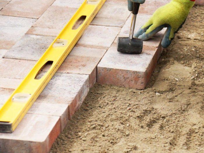 В процессе мощения не обойтись без резиновой киянки и строительного уровня